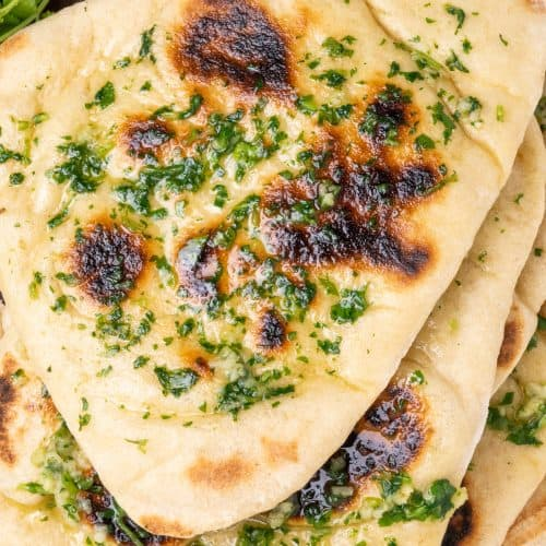 A stack of naan breads, with dark brown spots ono the top and brushed with garlic and coriander butter.