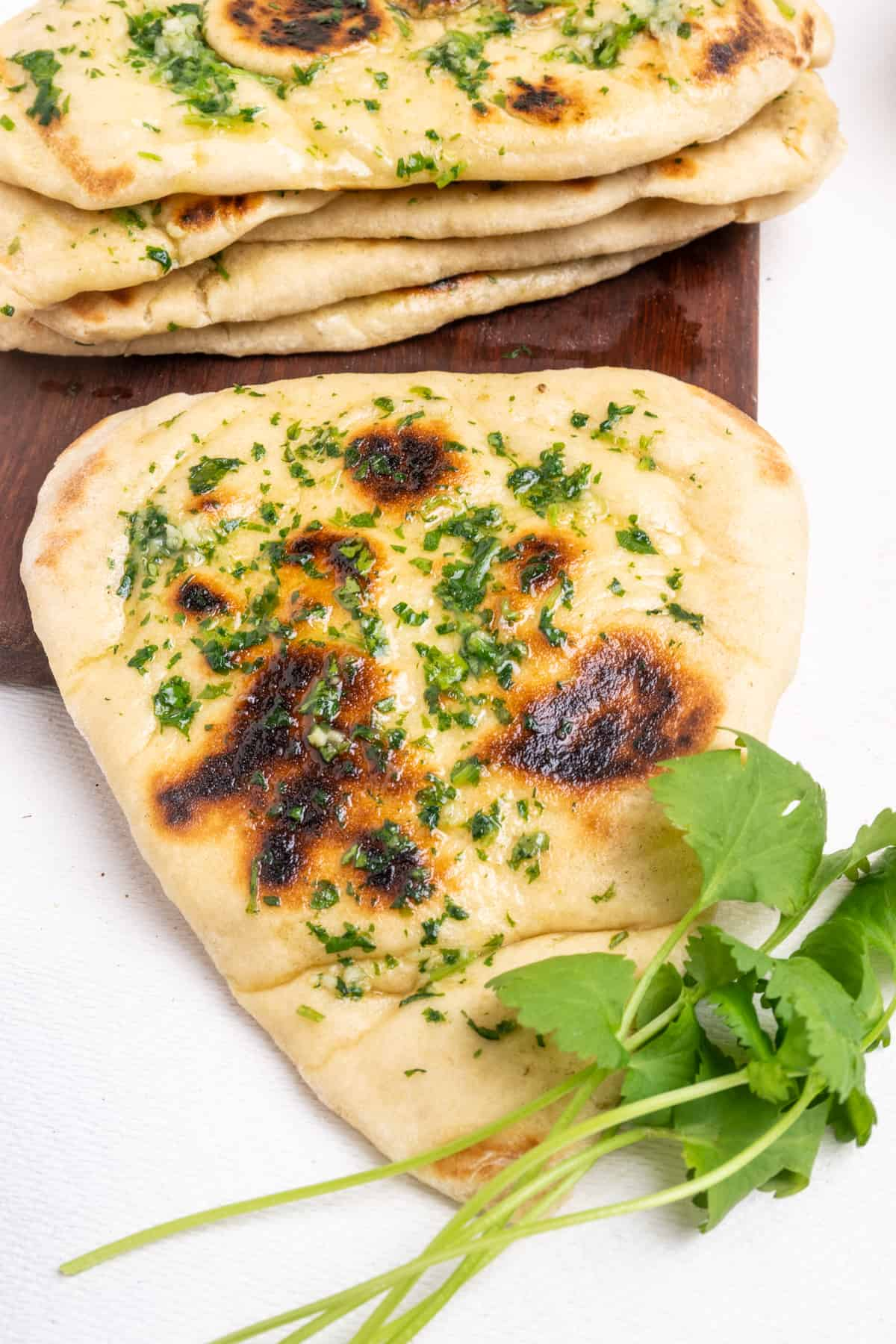 A naan bread with some fresh coriander greens, next to a stack of more flat breads.