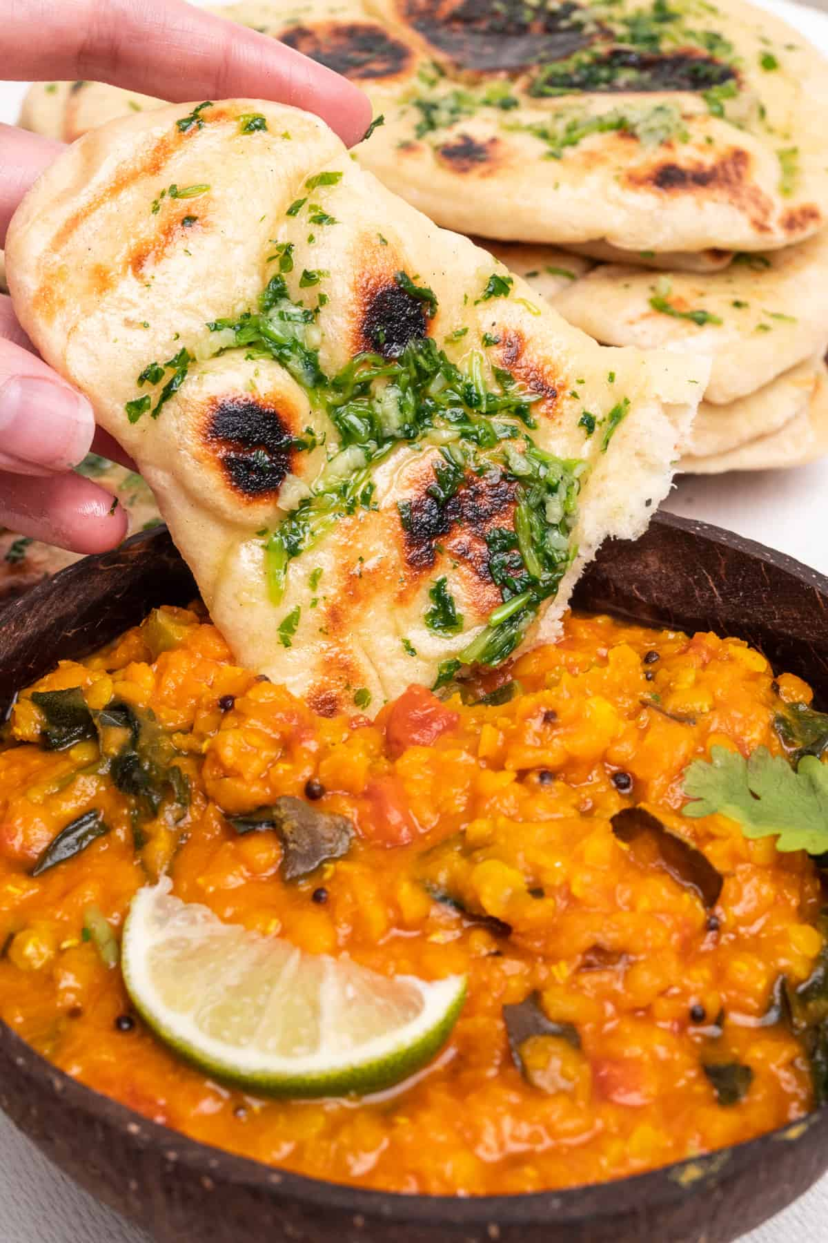 Garlic and coriander naan bread dipped into a red lentil curry. A perfect combination!