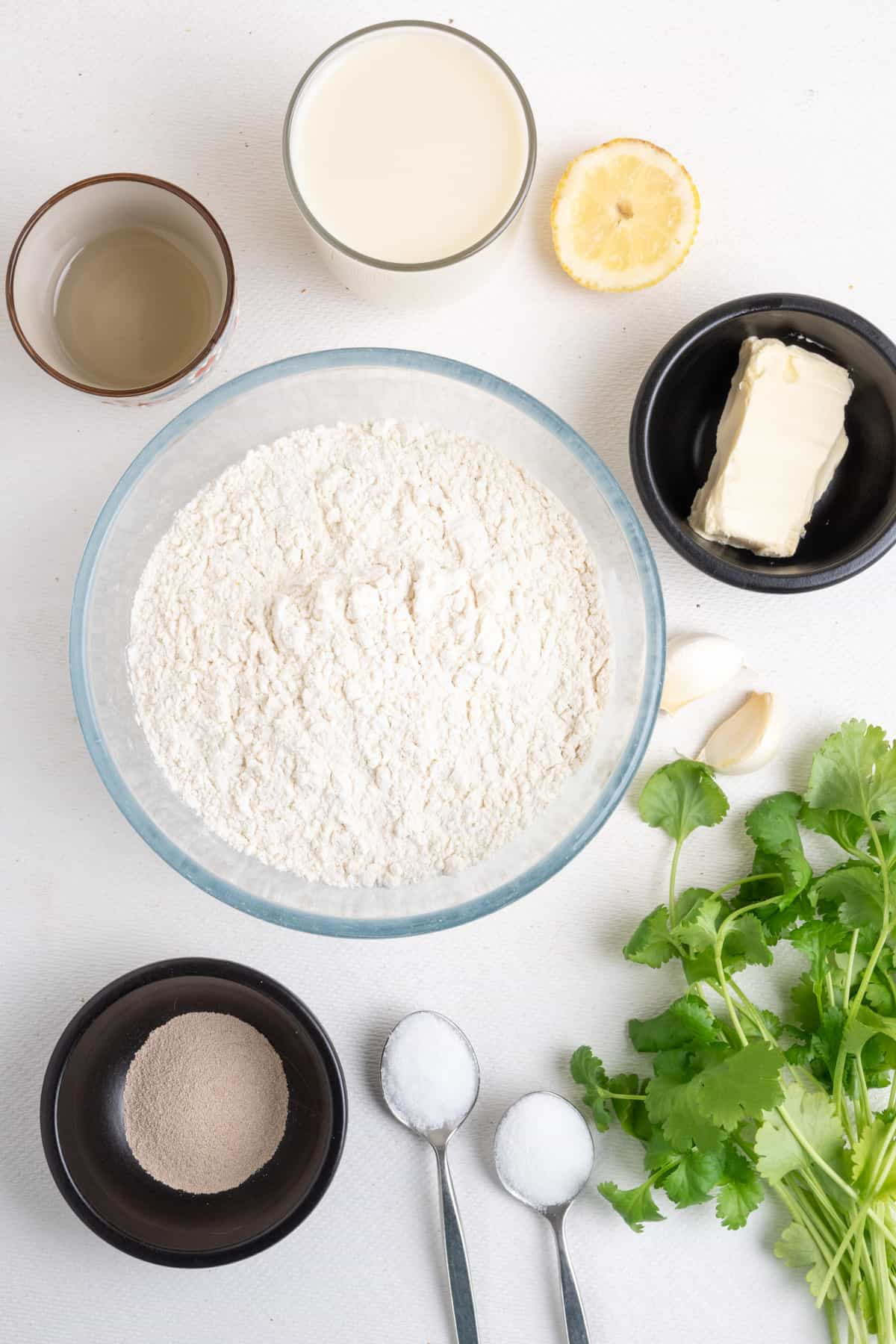 The ingredients for garlic and coriander naan: a bowl of plain flour surrounded by smaller pots of dried yeast, soy milk, vegetable oil, as well as a teaspoon each of sugar and salt, a slice of lemon, and some vegan butter, fresh coriander and two garlic cloves.