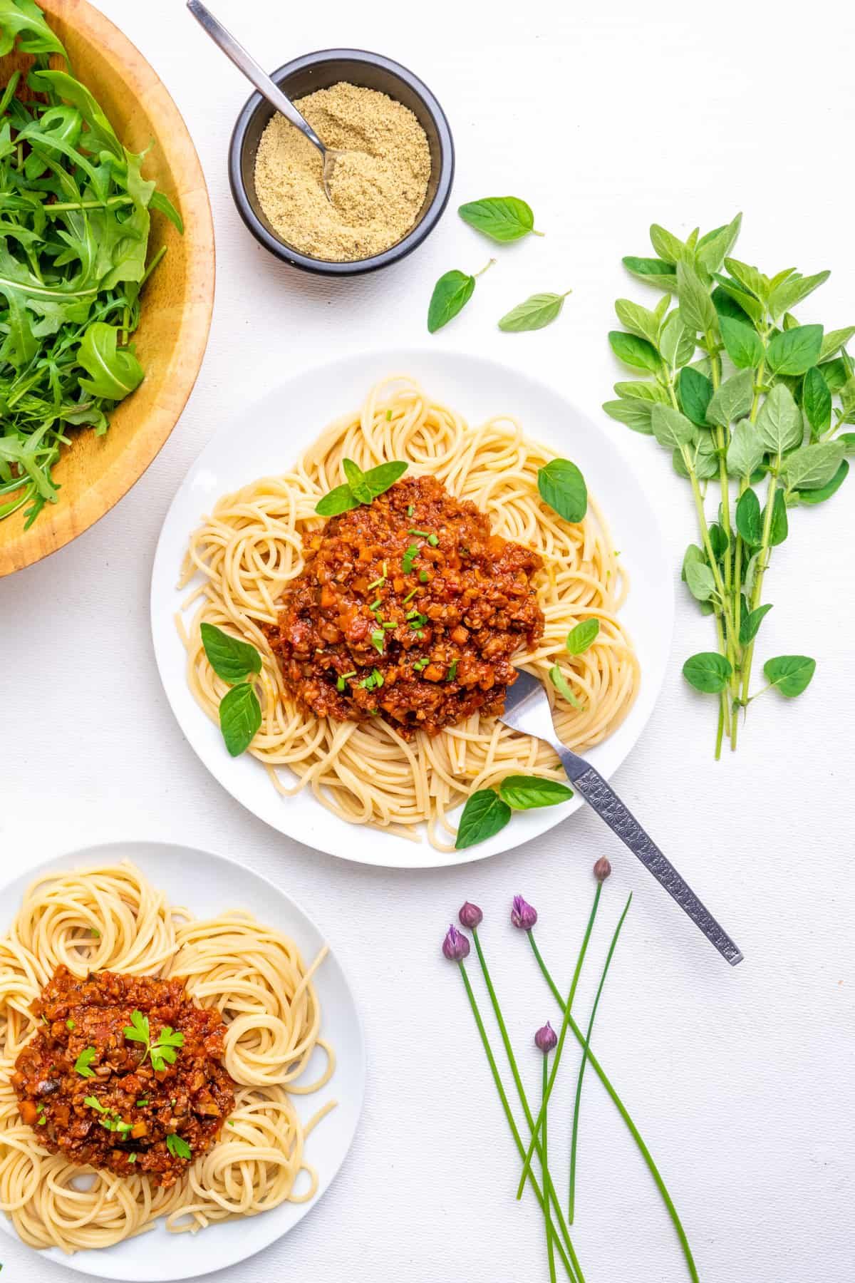 Top down view of a dining table. Two plates of spaghetti bolognese, a bunch of fresh herbs and chives, a small pot of vegan parmesan and a bowl of rocket.