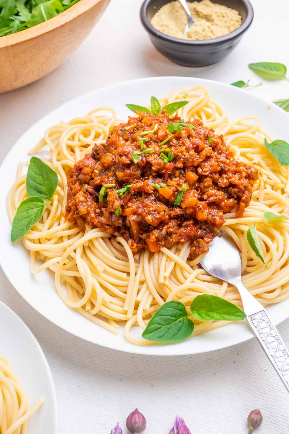 A plate of beautifully swirling spaghetti topped with a red bolognese sauce and served with salad and a ground vegan parmesan condiment.