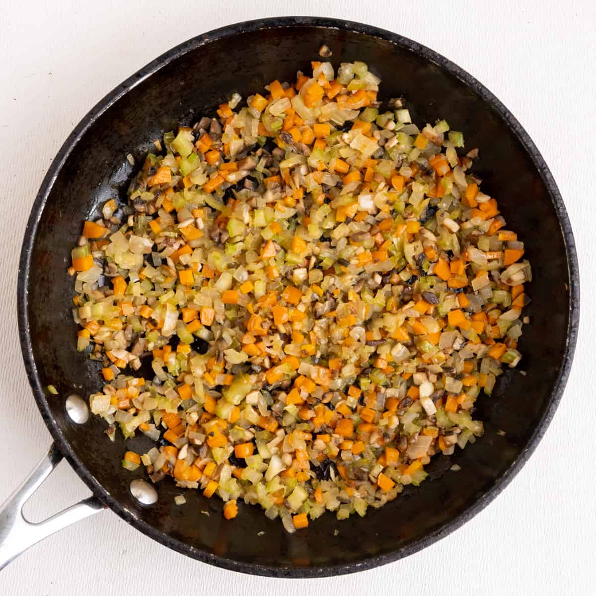 Sauteeing finely diced onion, carrots, celery and mushrooms in a frying pan.