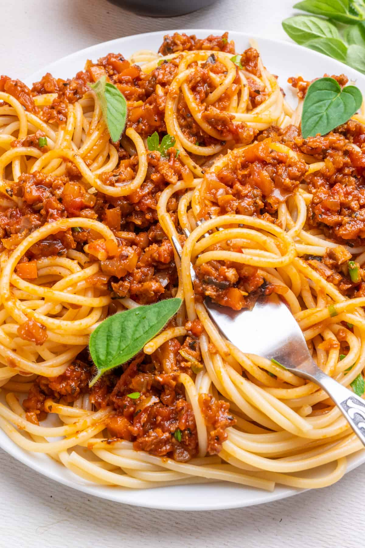 A fork digs into a plate of spaghetti bolognese.