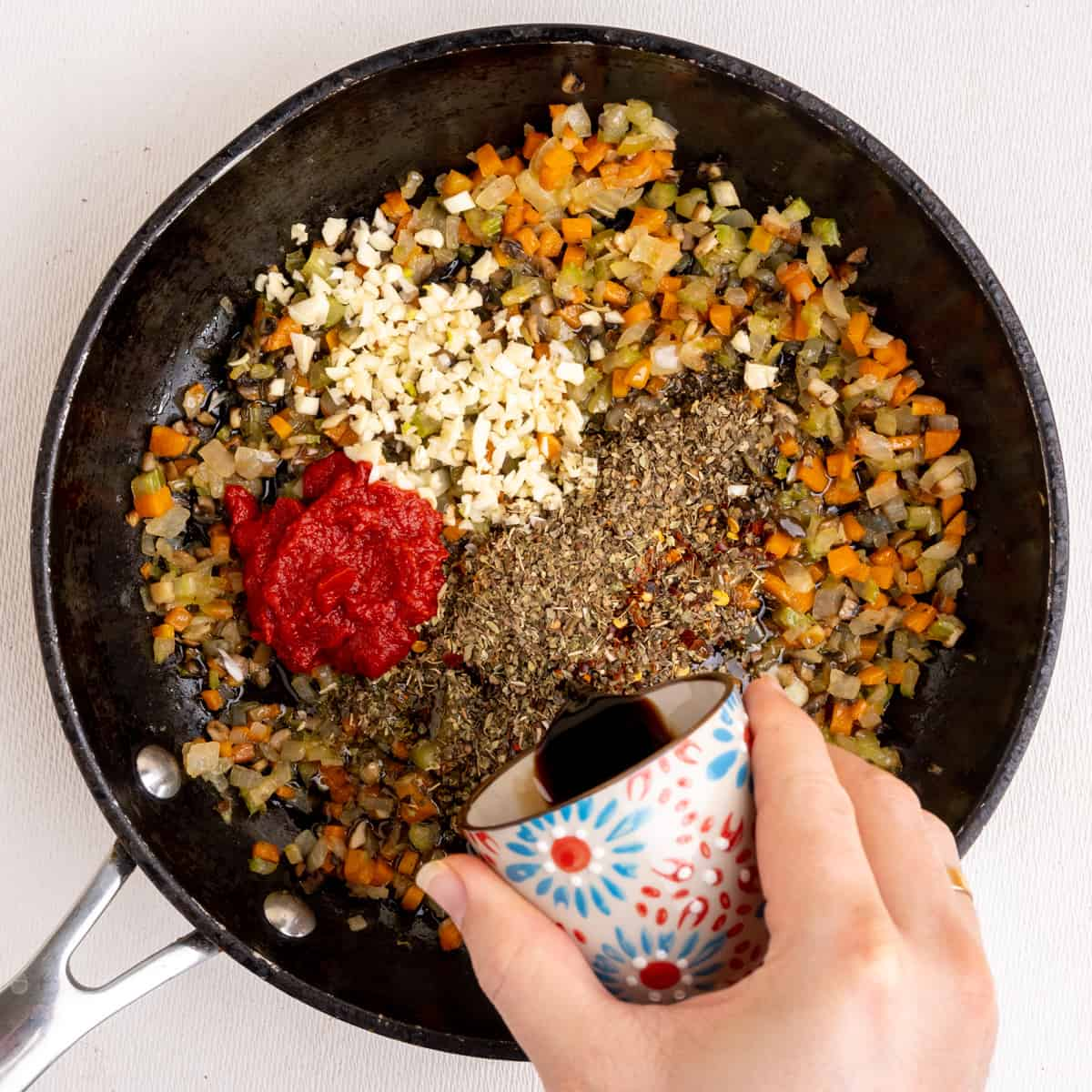 Garlic, dried herbs, tomato puree and other ingredients are added to the sauteed vegetables.