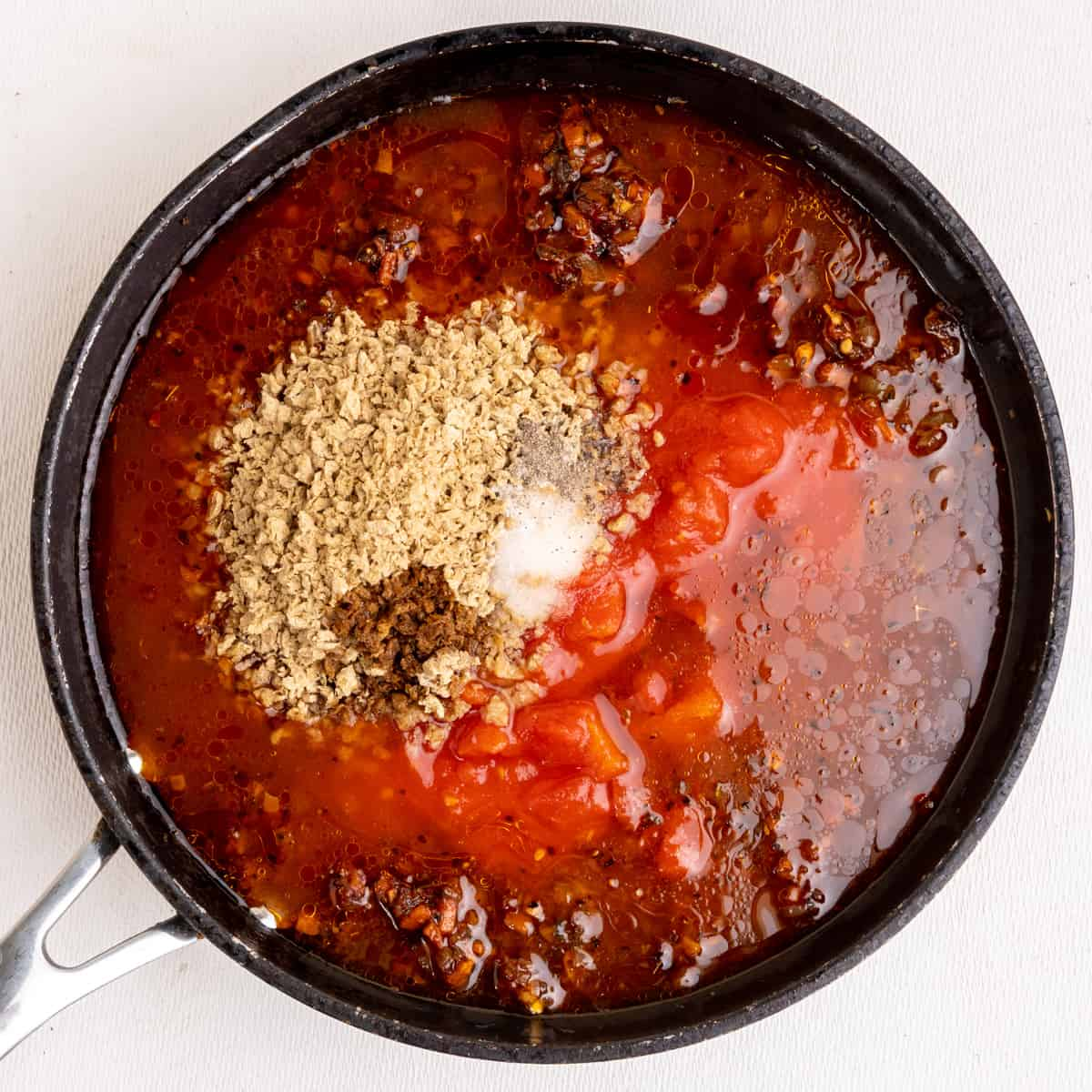 The dried soya mince, chopped tomatoes, soy sauce, salt and pepper and water are added to the reddish brown sauteed aromatic flavour base to make the bolognese sauce.