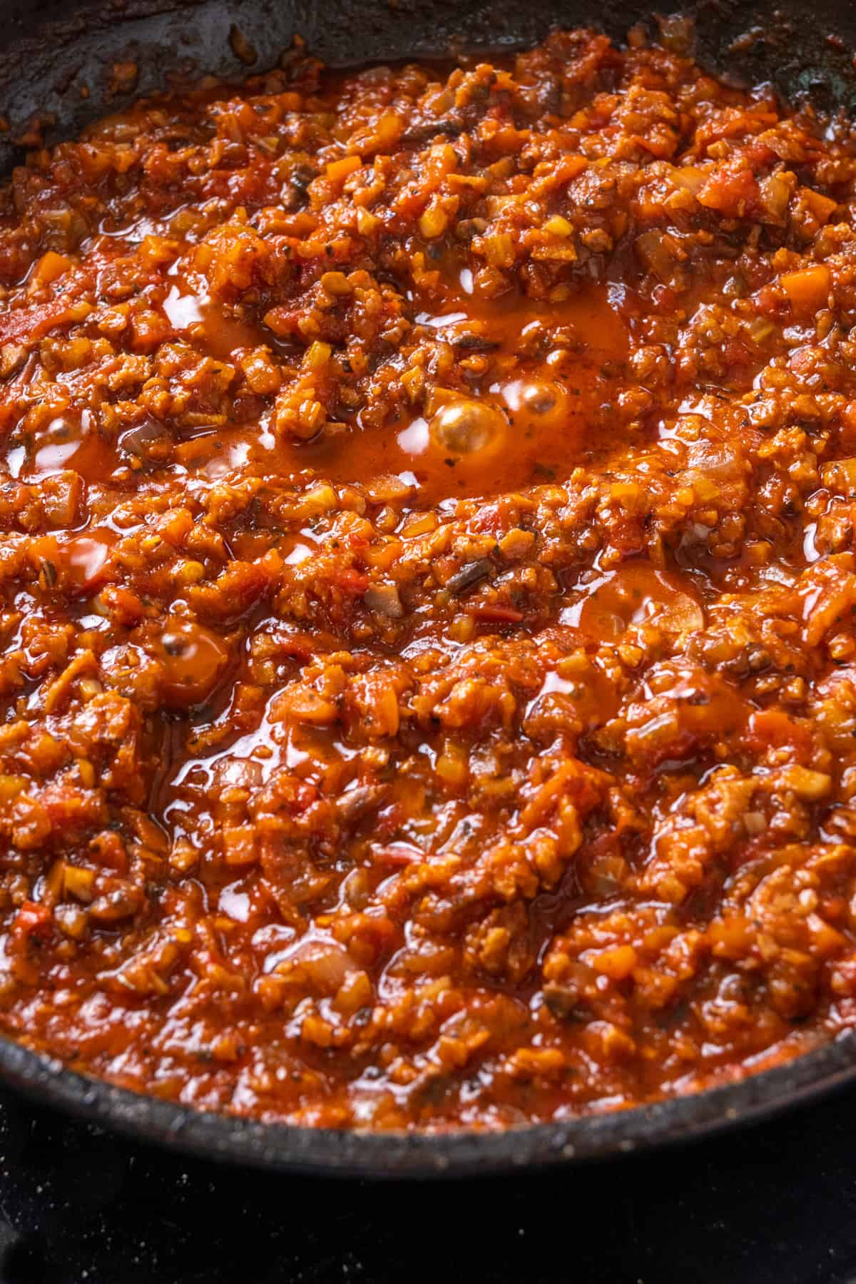 A thick and deep sauce with granular texture bubbling in a saucepan.