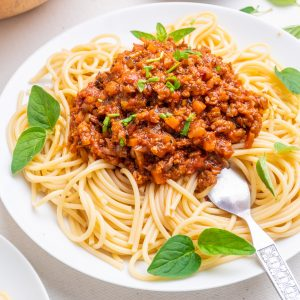 A plate of beautifully twisted spaghetti topped with a red bolognese sauce and garnished with chives fresh herbs.