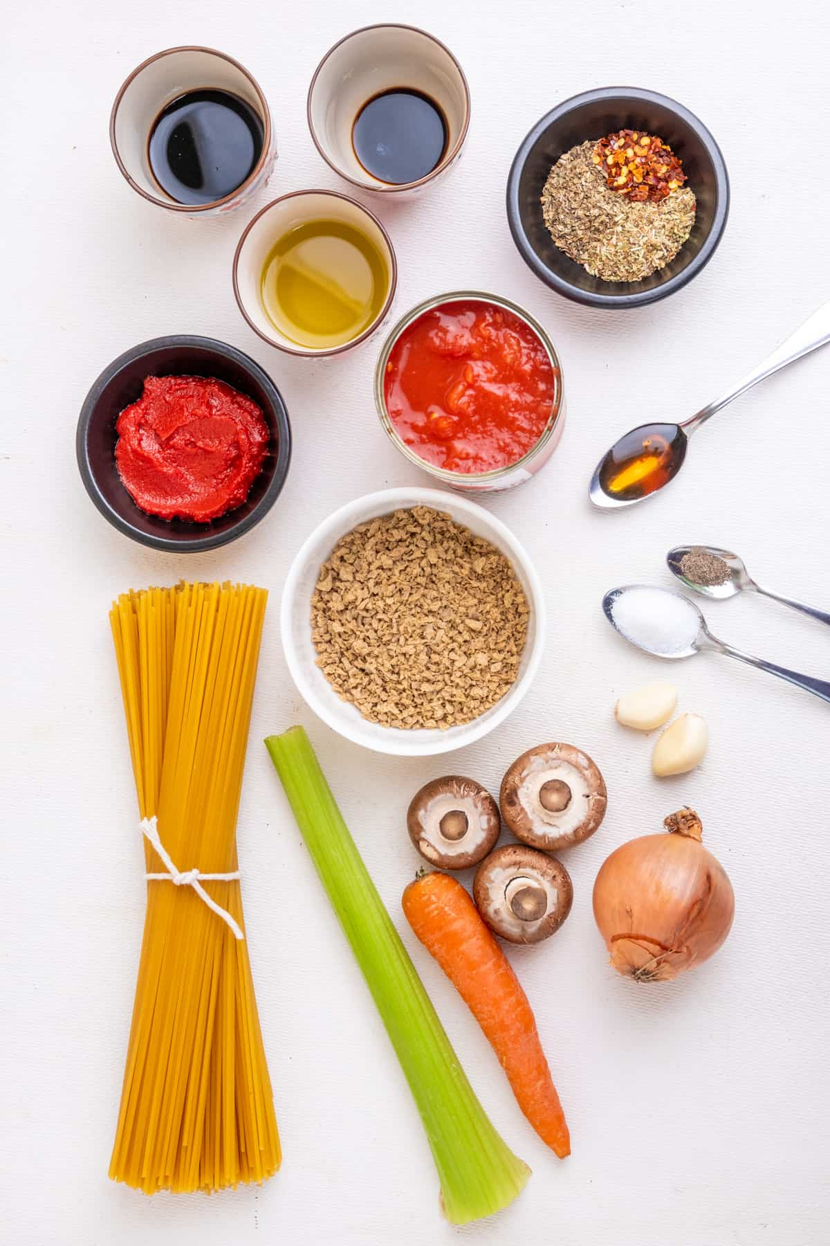 The ingredients for vegan bolognese. Dried soy mince provides the meaty texture. There's also some vegetables, chopped tomatoes, tomato puree, olive oil, herbs and various condiments and dry ingredients for seasoning.