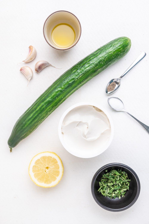 The ingredients for vegan tzatziki: Thick 'Greek style' vegan yoghurt, a cucumber, fresh garlic, lemon juice, fresh mint, olive oil, salt and black pepper.