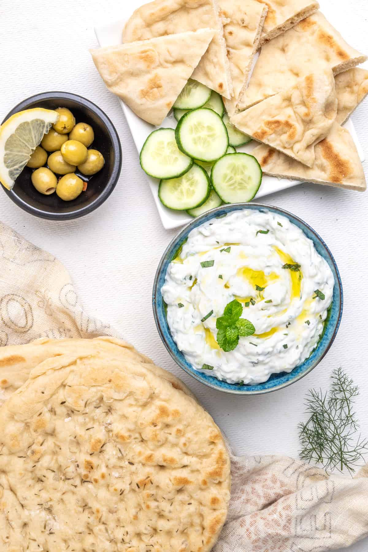 a bowl of tzatziki, drizzled with olive oil and decorated with a sprig of fresh mint, served up with pita bread, olives and slices of cucumber.