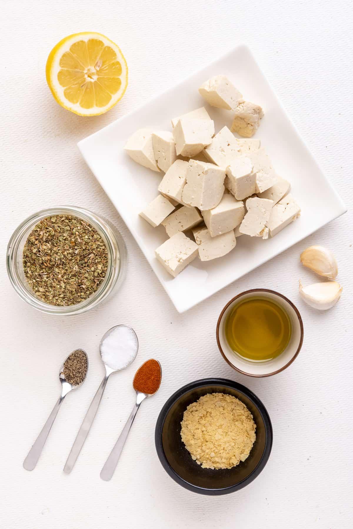 The ingredients for vegan souvlaki: Cubed firm tofu, olive oil, a half lemon, oregano, fresh garlic, salt, pepper, paprika and nutritional yeast.
