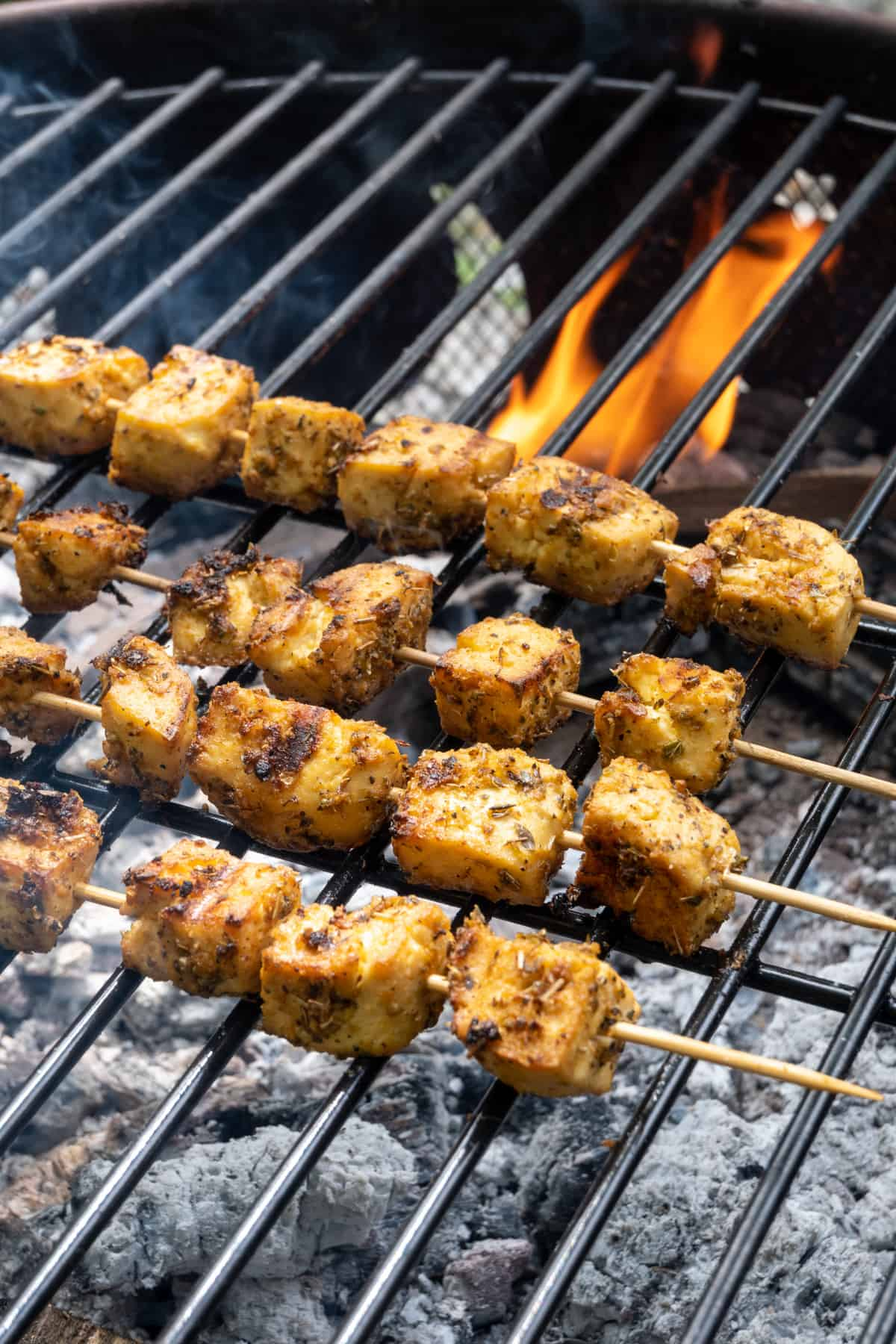 Tofu skewers on a roast over a firepit after cooking. The tofu looks golden brown, lightly crispy and is gently charred in some places.