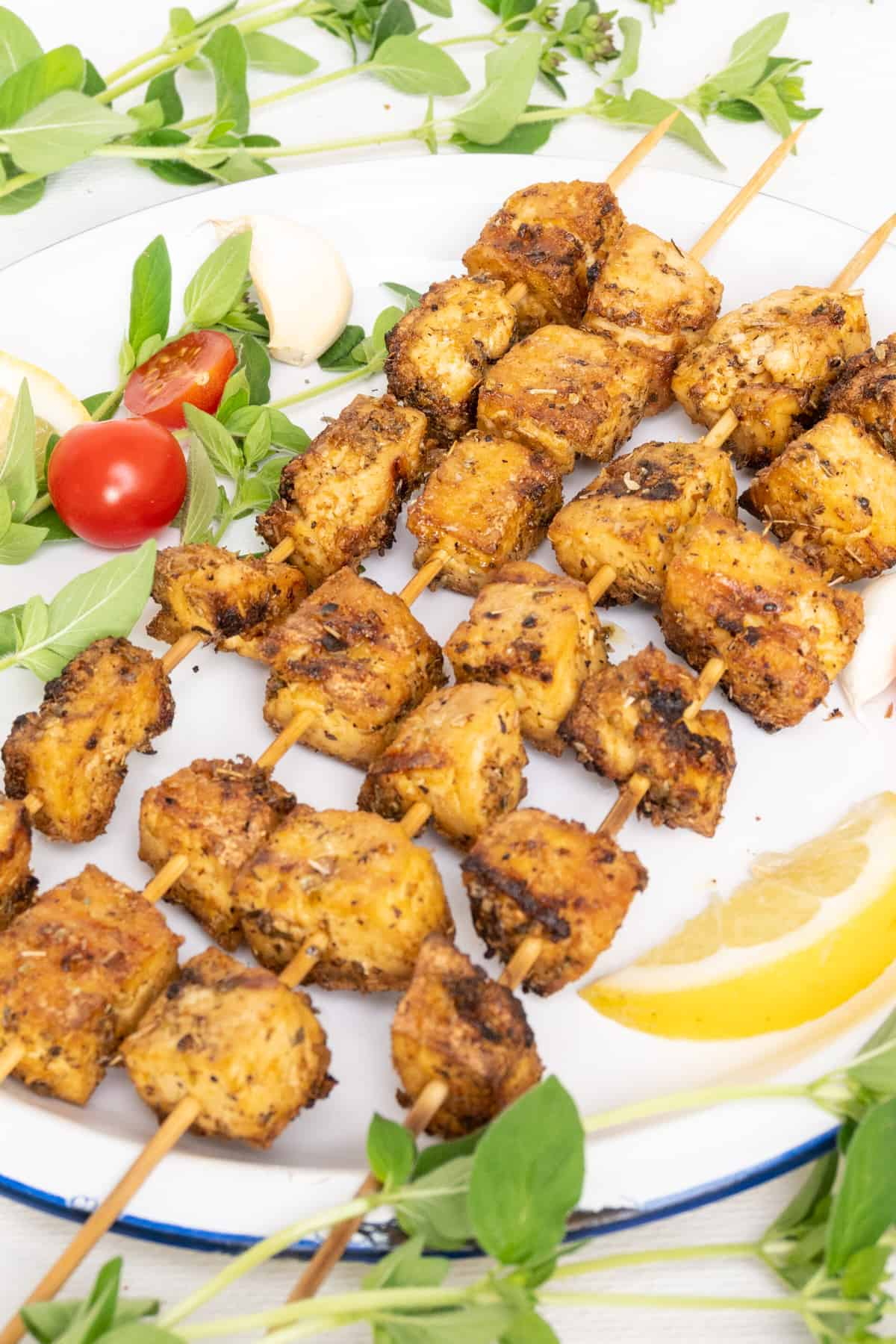 Grilled skewers of marinated tofu served on a plate with fresh oregano, cherry tomatoes, a wedge of lemon, plus a clove of garlic as decoration.