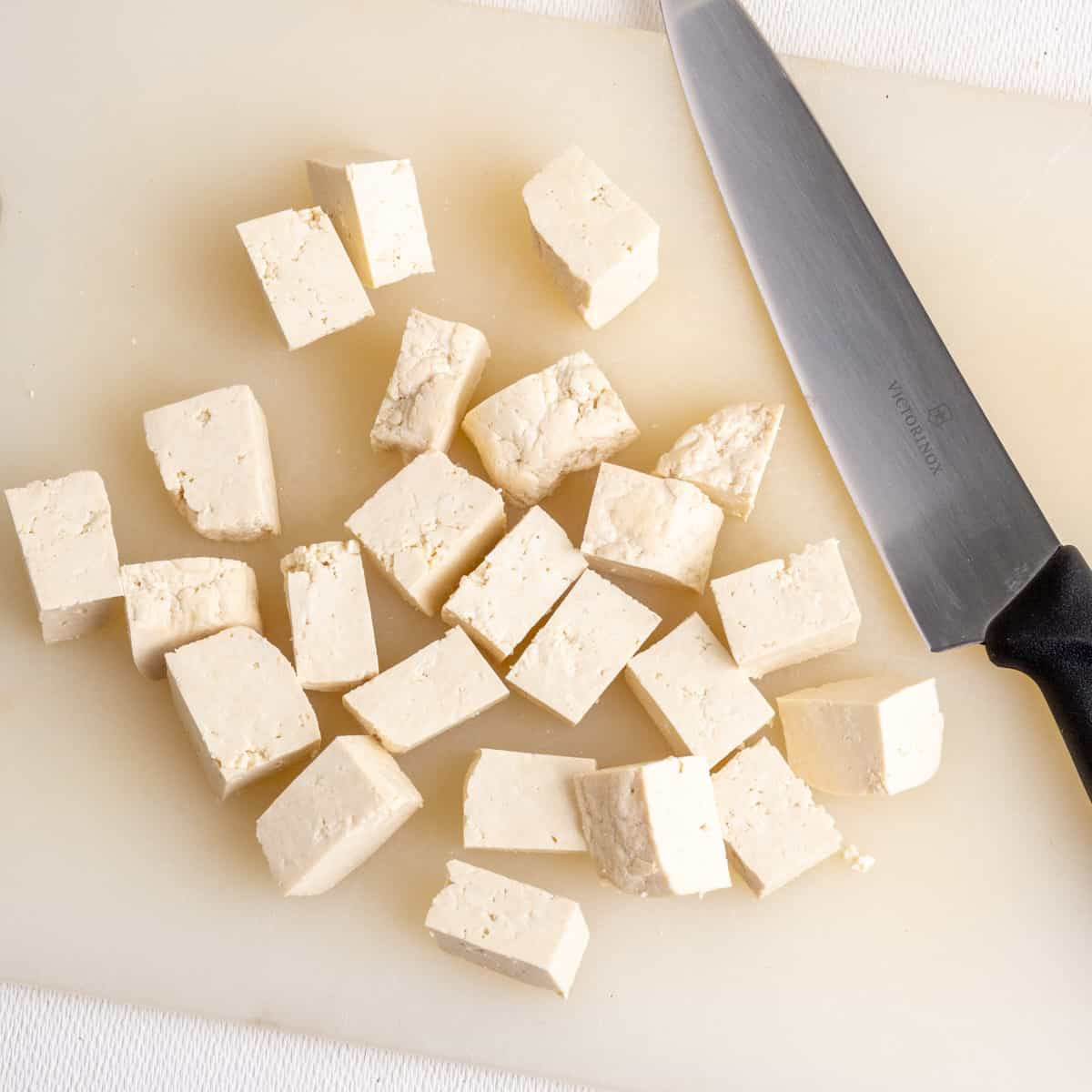 Cubes of firm tofu with kitchen knife on a white chopping board.