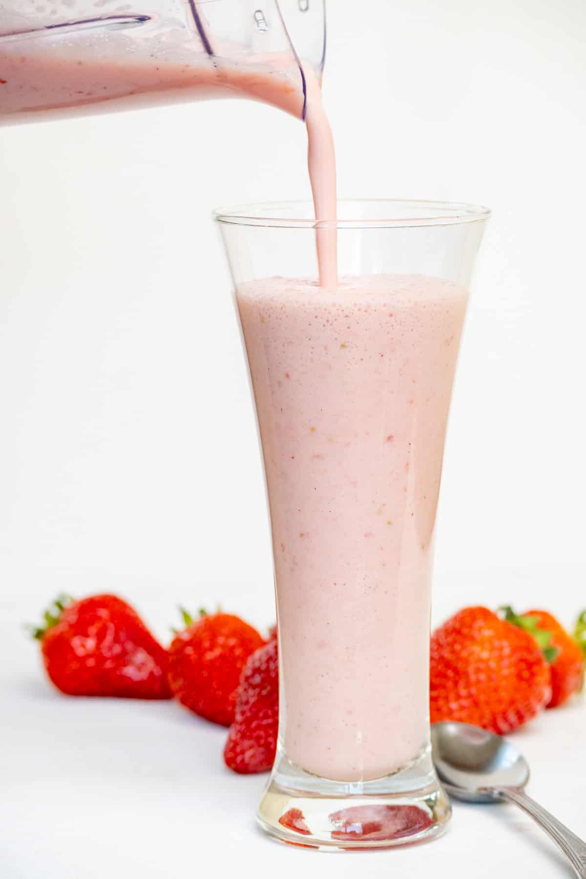Light pink milkshake is poured into a tall fluted glass.