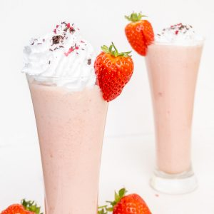 Two glasses of strawberry milkshake, decorated with whipped cream and whole strawberries.