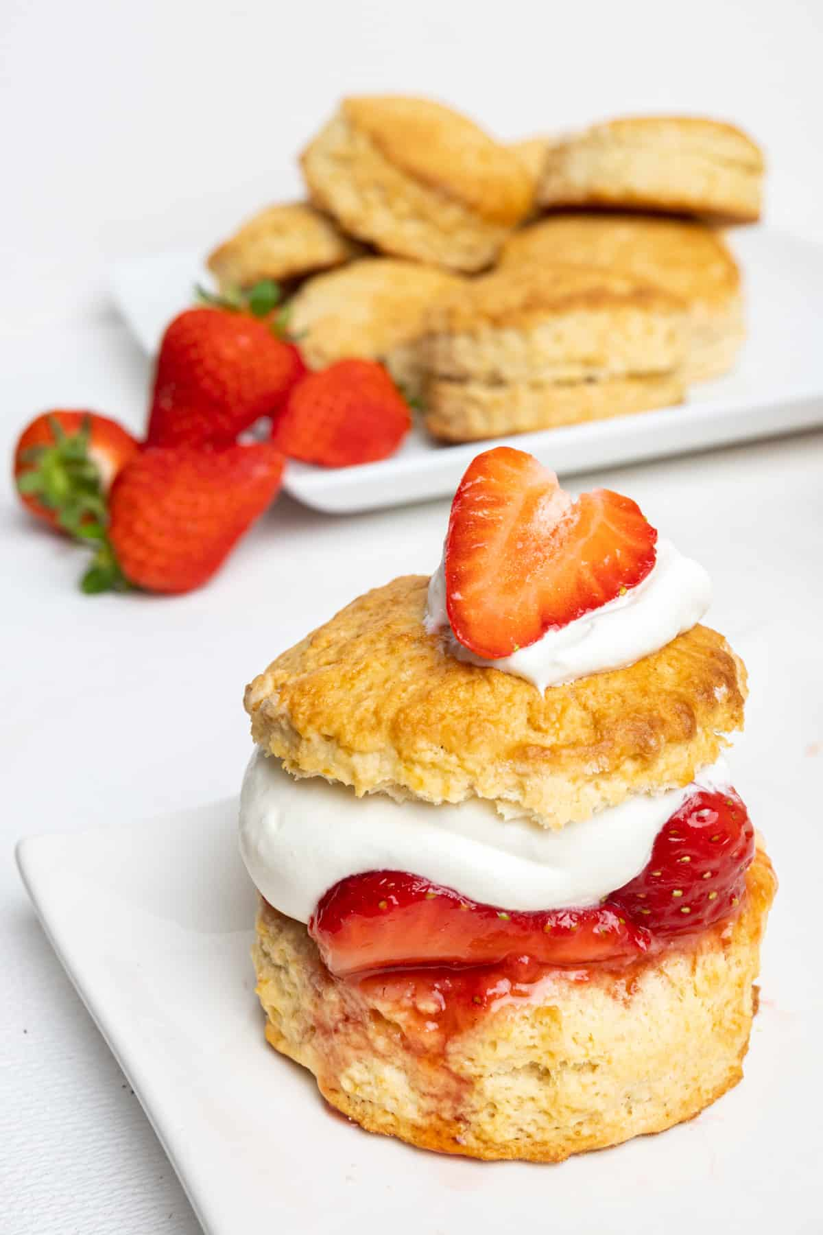 A golden baked biscuit filled with strawberries and whipped cream. The juice from the fruit is running down the side of the biscuit base.