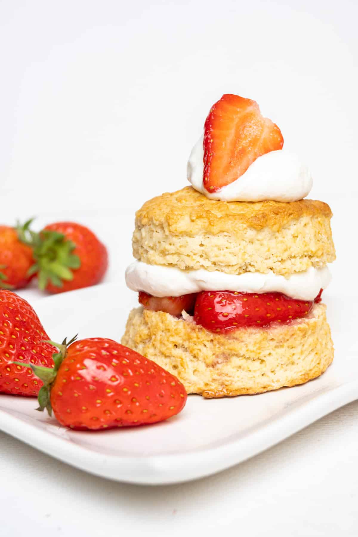 Two layers of golden baked biscuit are filled with juicy strawberries and whipped cream. The top biscuit is topped with more cream and a fresh strawberry.