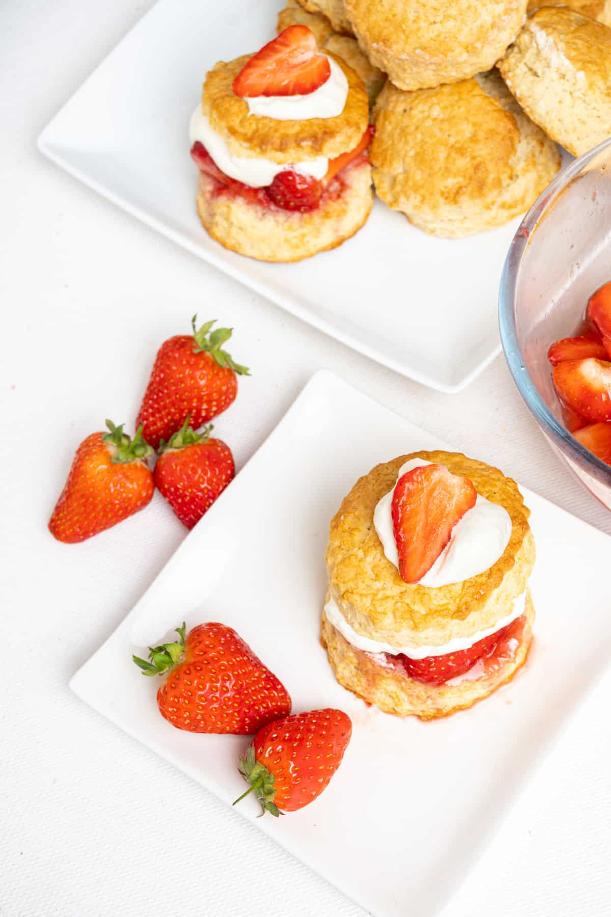 A tall biscuit with a cream and strawberry filling and topping served on a plate with fresh strawberries. More shortcakes on a serving platter in the back.