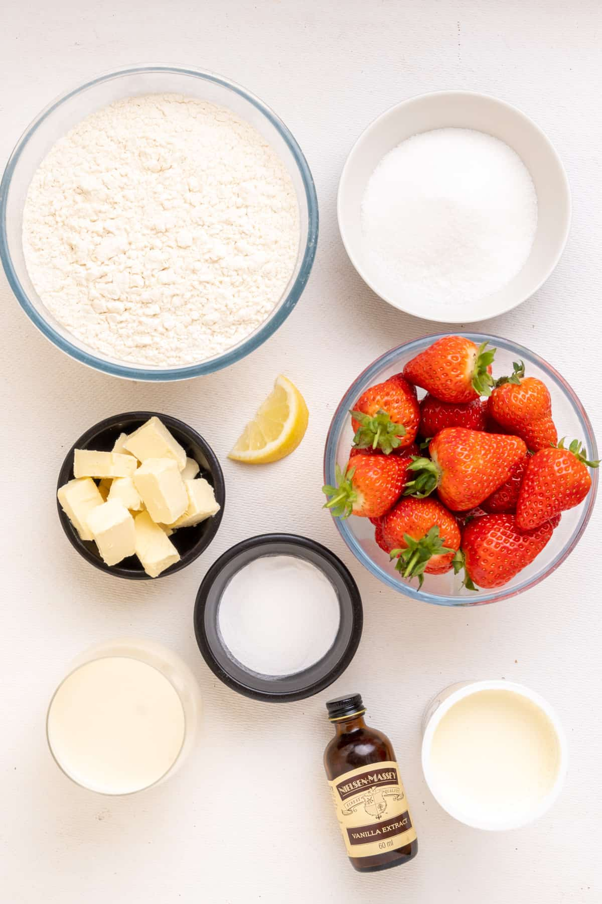 The ingredients for vegan strawberry shortcake: Strawberries, white flour, sugar, baking powder, cubes of vegan butter, soy milk, vegan whipping cream, vanilla extract and a small piece of lemon.