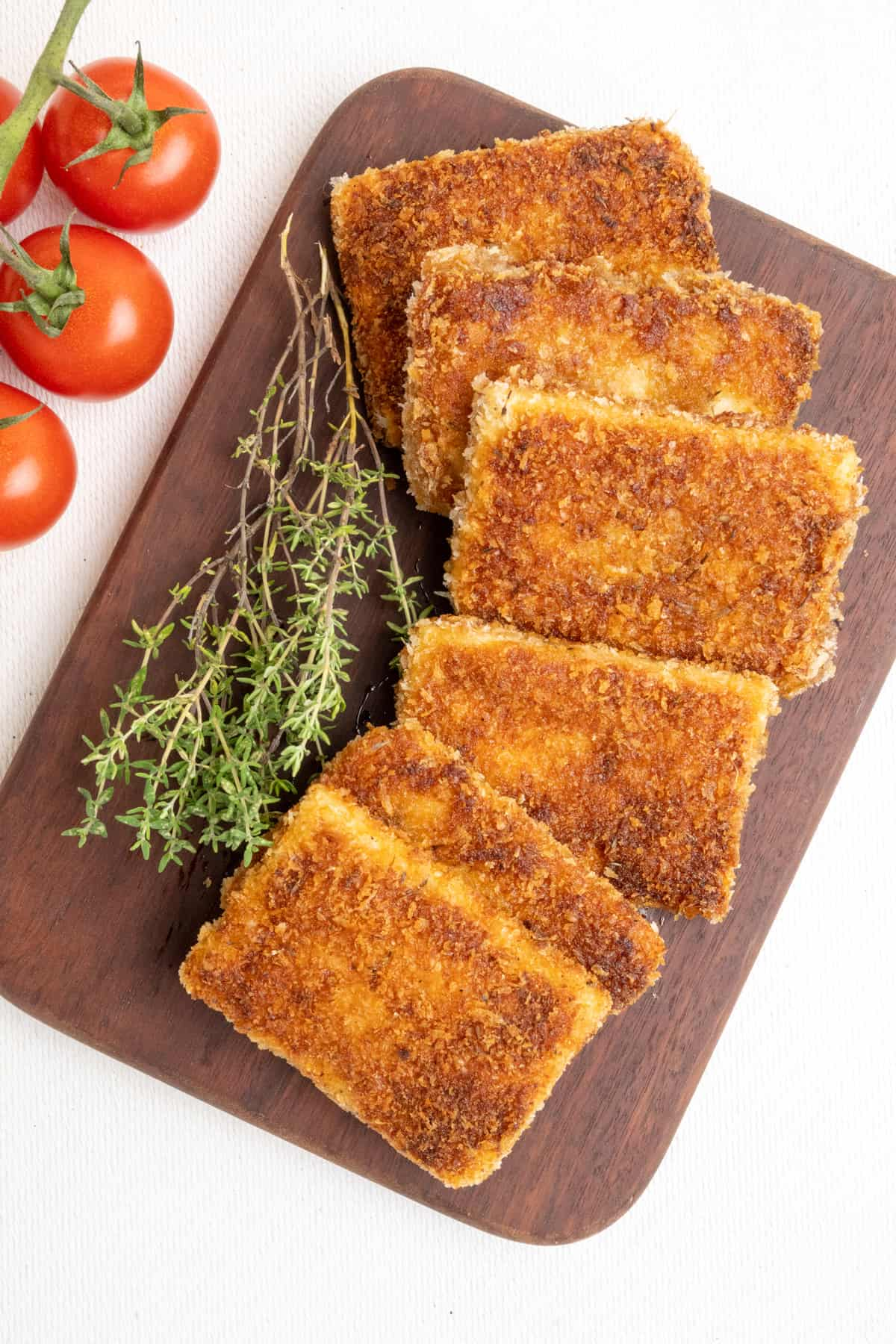Rectangular slices of breaded and fried tofu arranged on a dark wooden board.