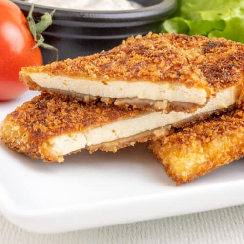 The image depicts the crispy fried crust of golden brown breadcrumbs and the tender inside texture of a slice of breaded tofu cut in two.