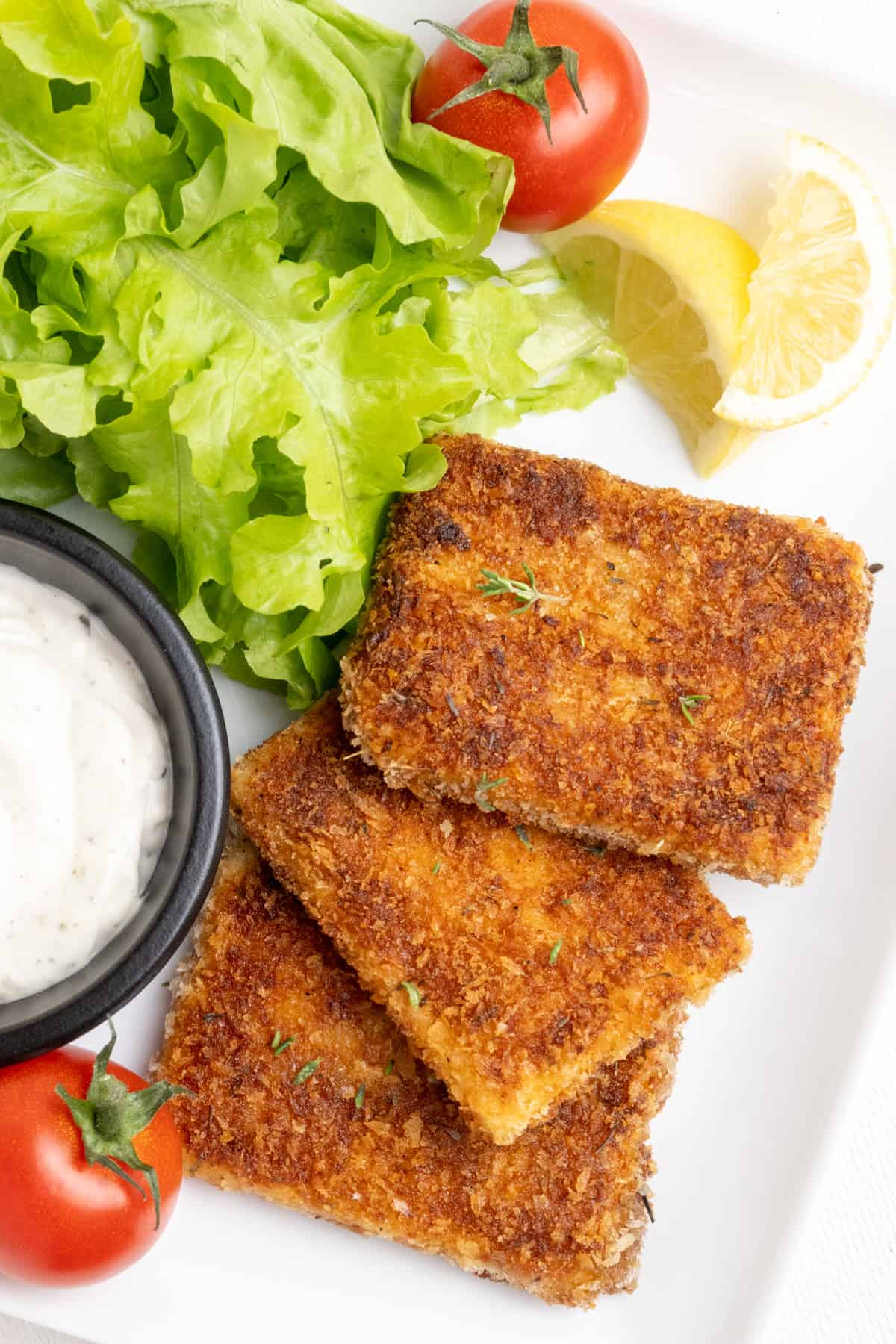 Slices of golden brown breaded tofu served on a white plate with lettuce, tomatoes, wedges of lemon and a white dipping sauce.