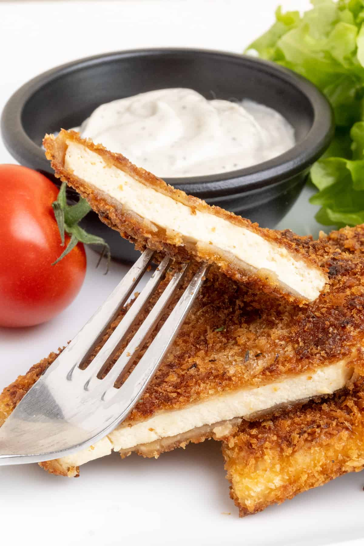 A corner piece of breaded tofu cut from a slice picked up on a fork.