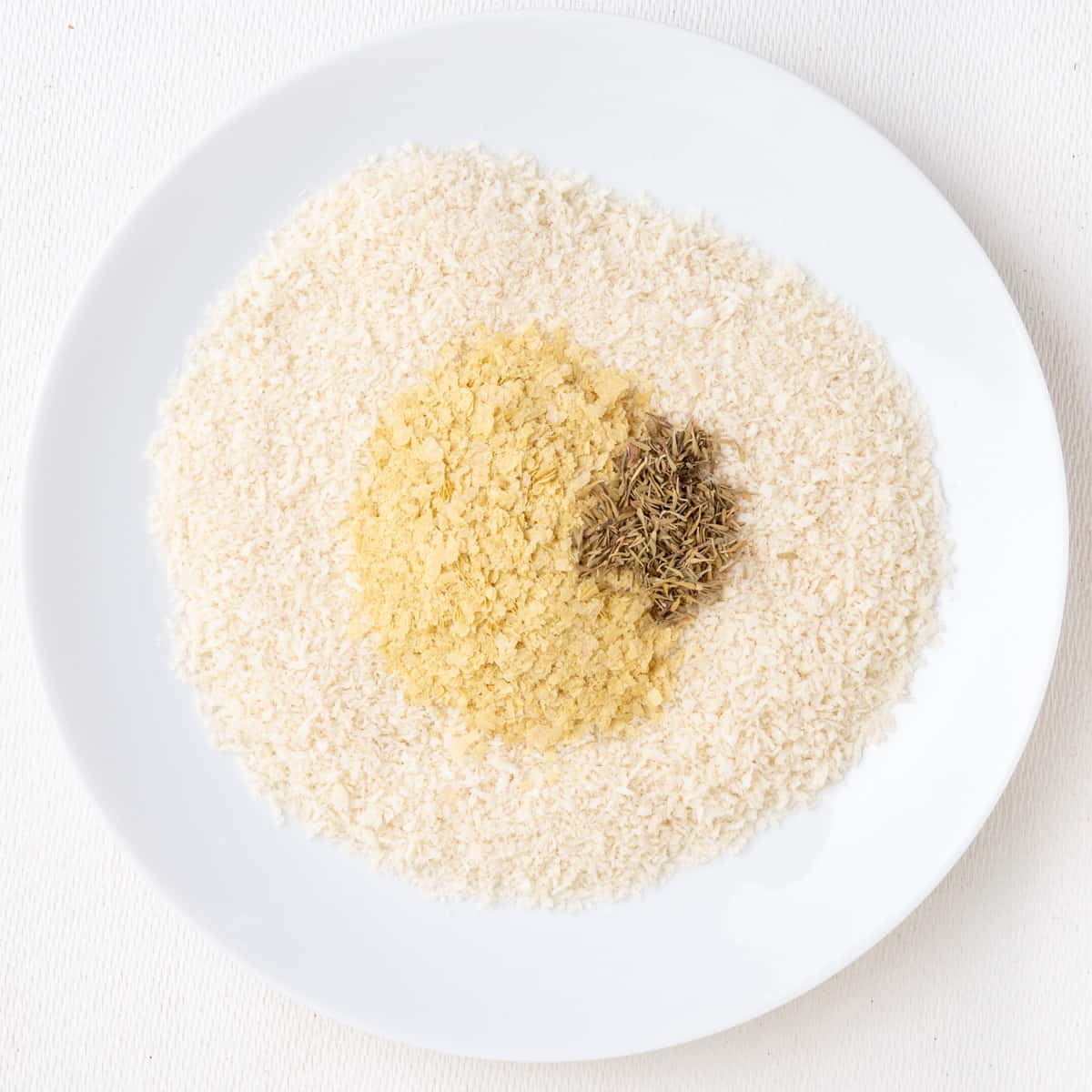 White breadcrumbs with nutritional yeast flakes and dried thyme on a shallow plate.
