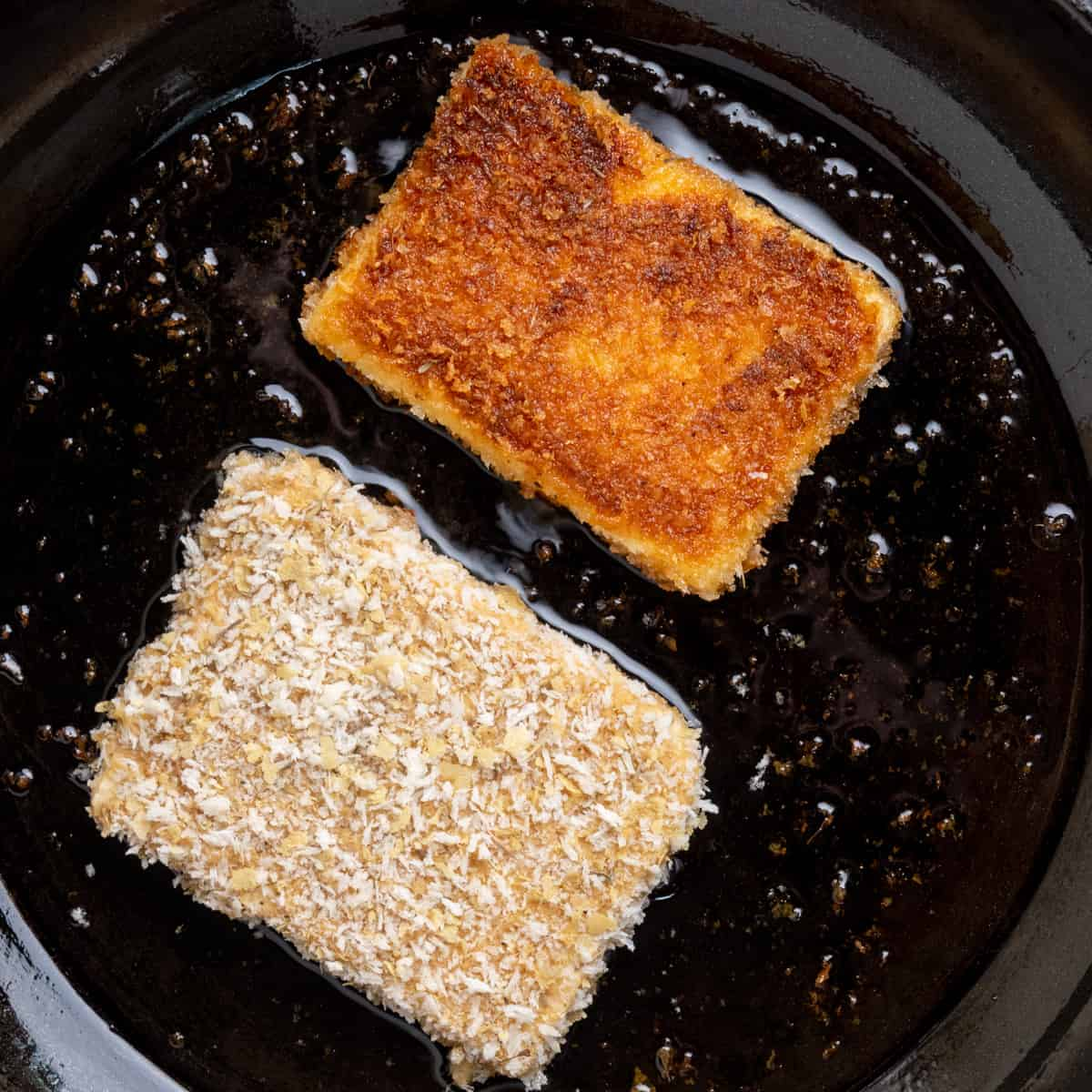 Two slices of tofu coated in breadcrumbs in a frying pan. One is pale on top, the other golden brown after being turned over in the pan.