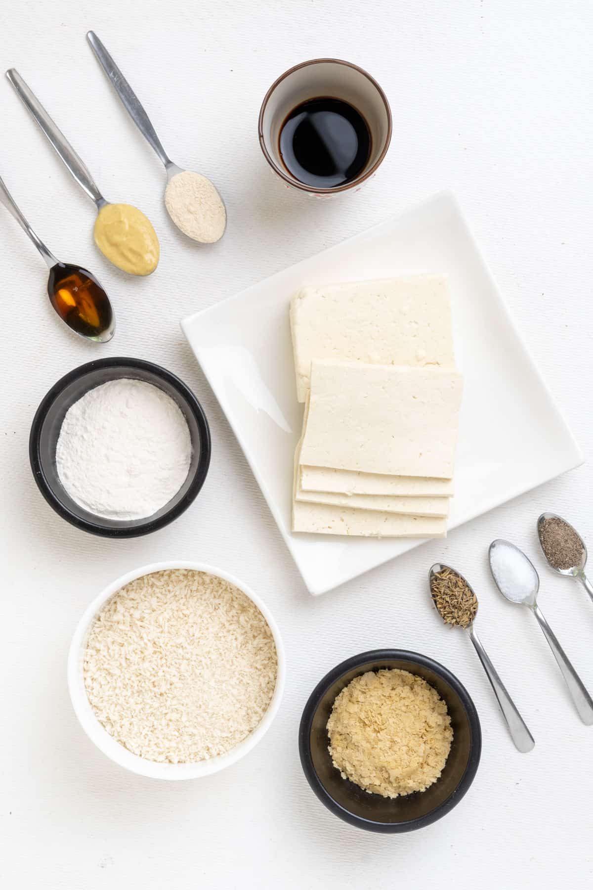 The ingredients for the breaded tofu recipe: Slices of firm tofu, plain flour, Japanese panko breadcrumbs, nutritional yeast flakes, soy sauce and on several spoons: maple syrup, dijon mustard, garlic powder, salt, pepper and dried thyme.