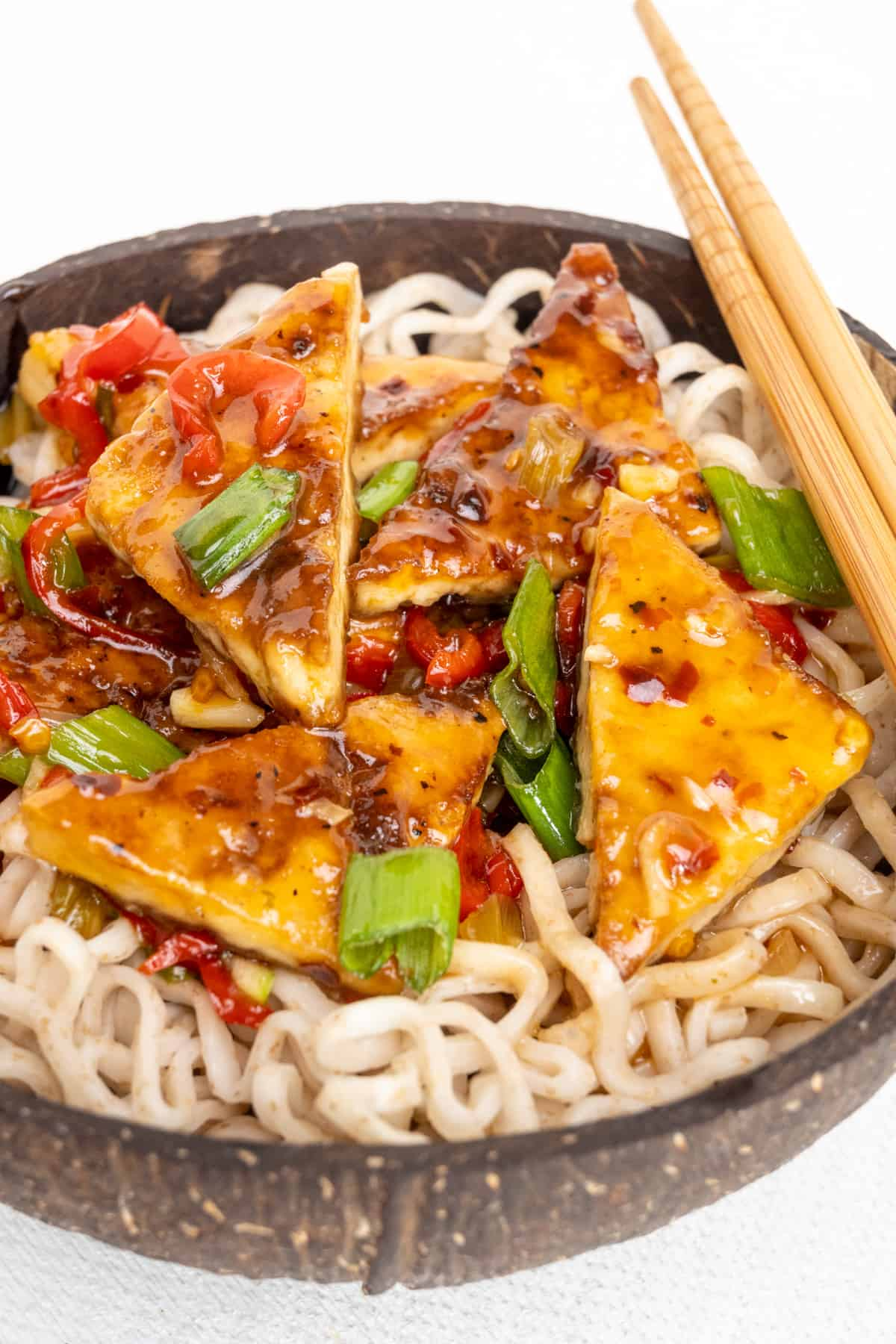 Noodles topped with fried tofu pieces covered in sweet chilli sauce in a bowl with chopsticks.