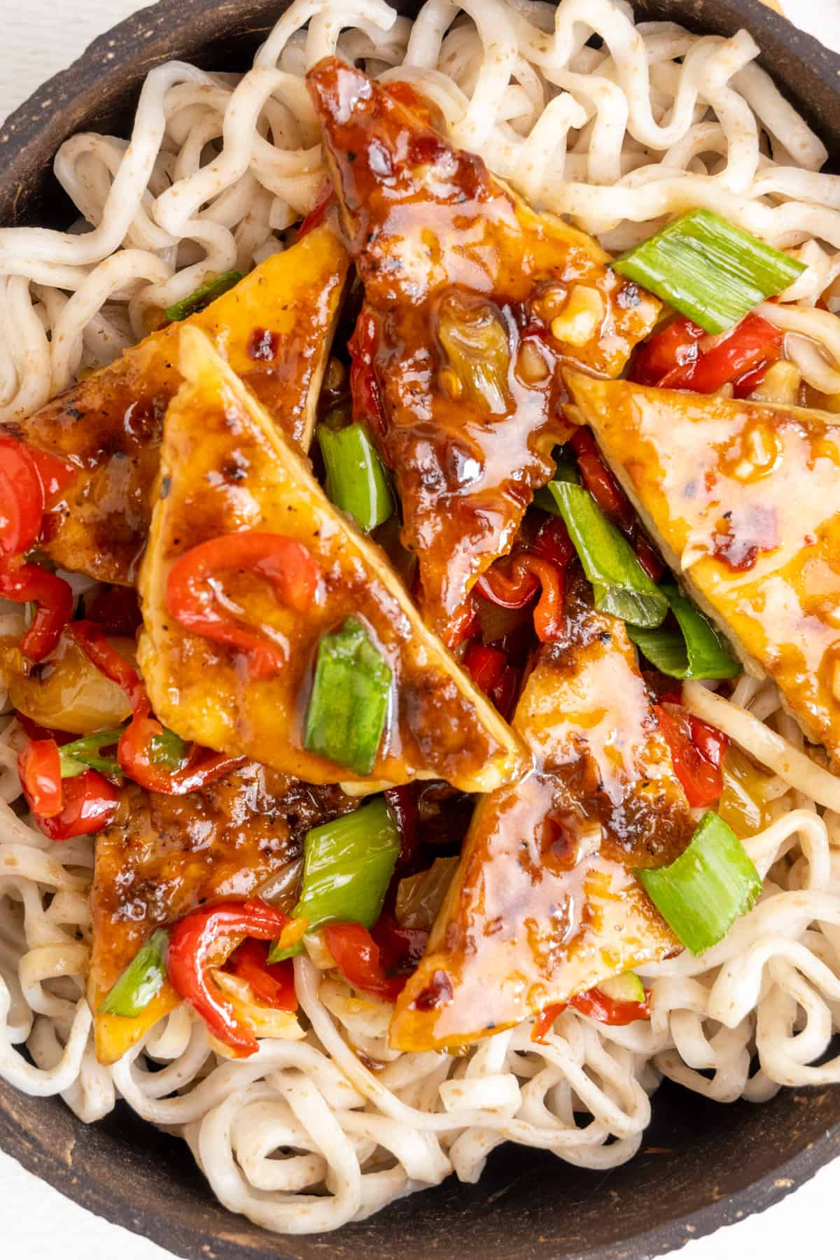 Triangular pieces of fried tofu covered in a sticky and glossy sauce and thinly sliced red pepper and spring onion greens on a bed of noodles.