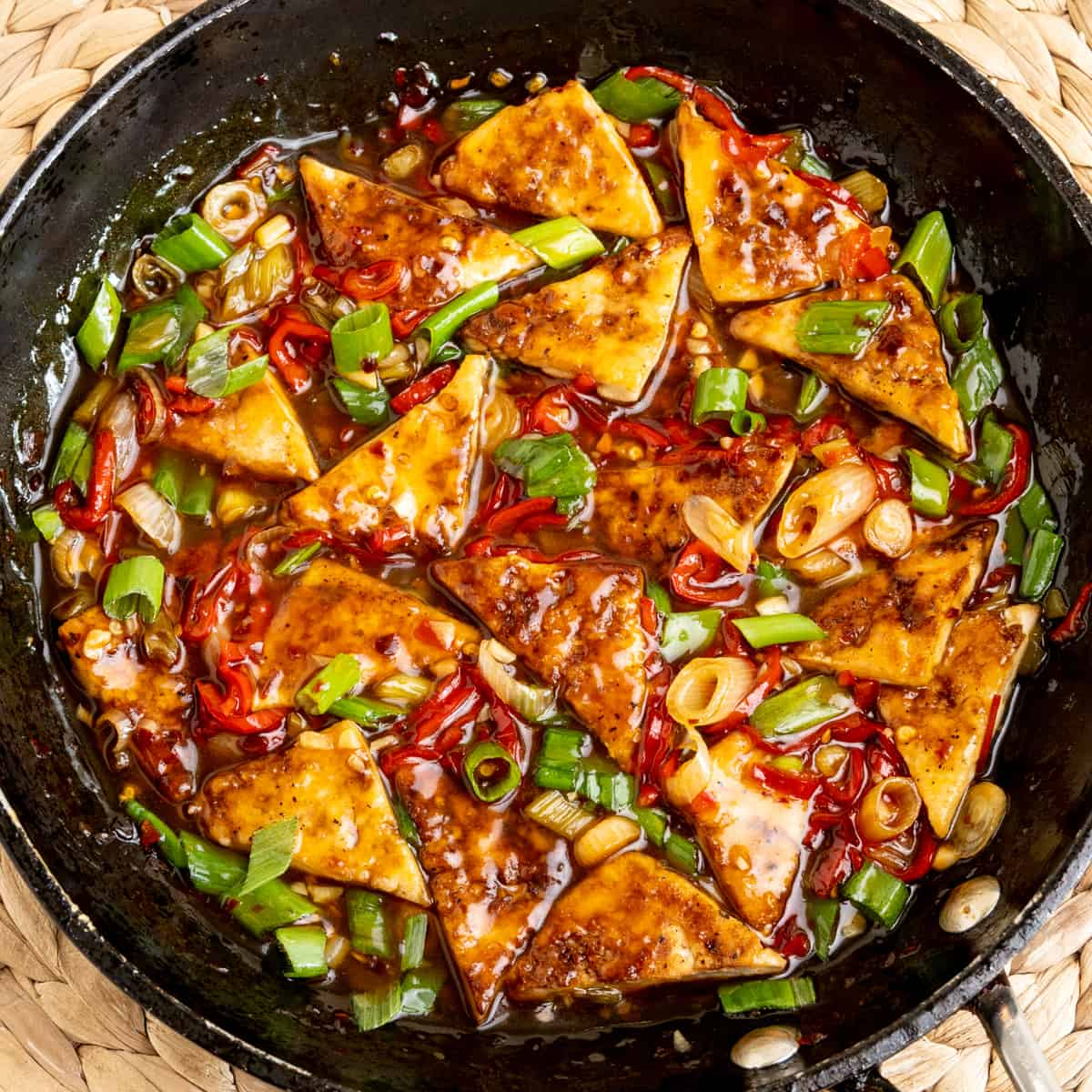 Pieces of fried tofu in a frying pan full of a colourful sauce with pieces of red pepper and spring onions.