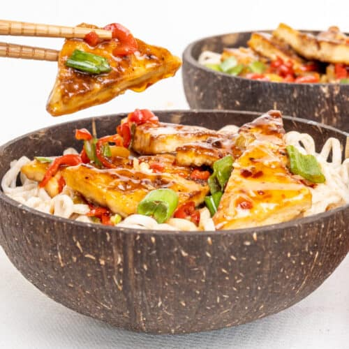 Chop sticks holding a triangular piece of fried tofu covered in a glossy sauce, above a bowl of food.