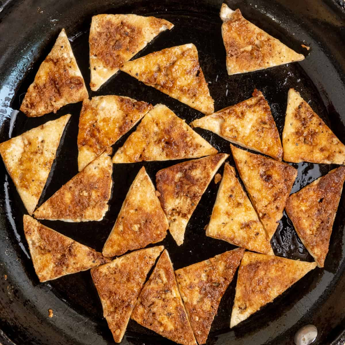 Triangular pieces of golden fried tofu in a frying pan.