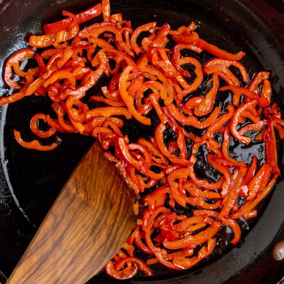 Sliced red pepper being fried in a frying pan.
