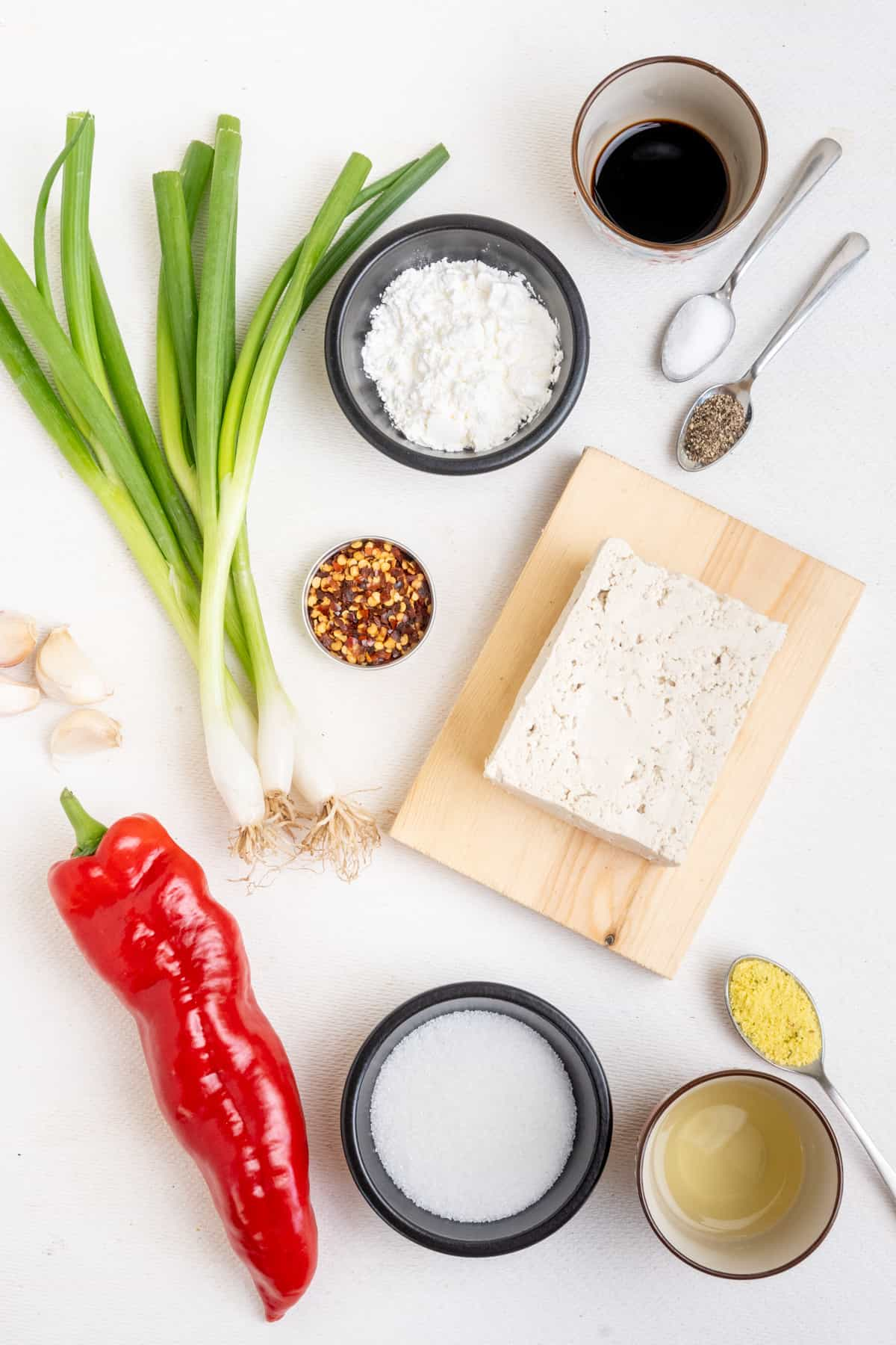 The ingredients used in this recipe for tofu in a sweet chili sauce, laid out on a white surface.