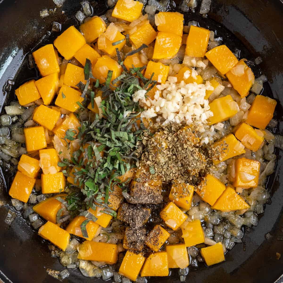 Garlic and herbs on top of sauteed butternut and onion in a pan.