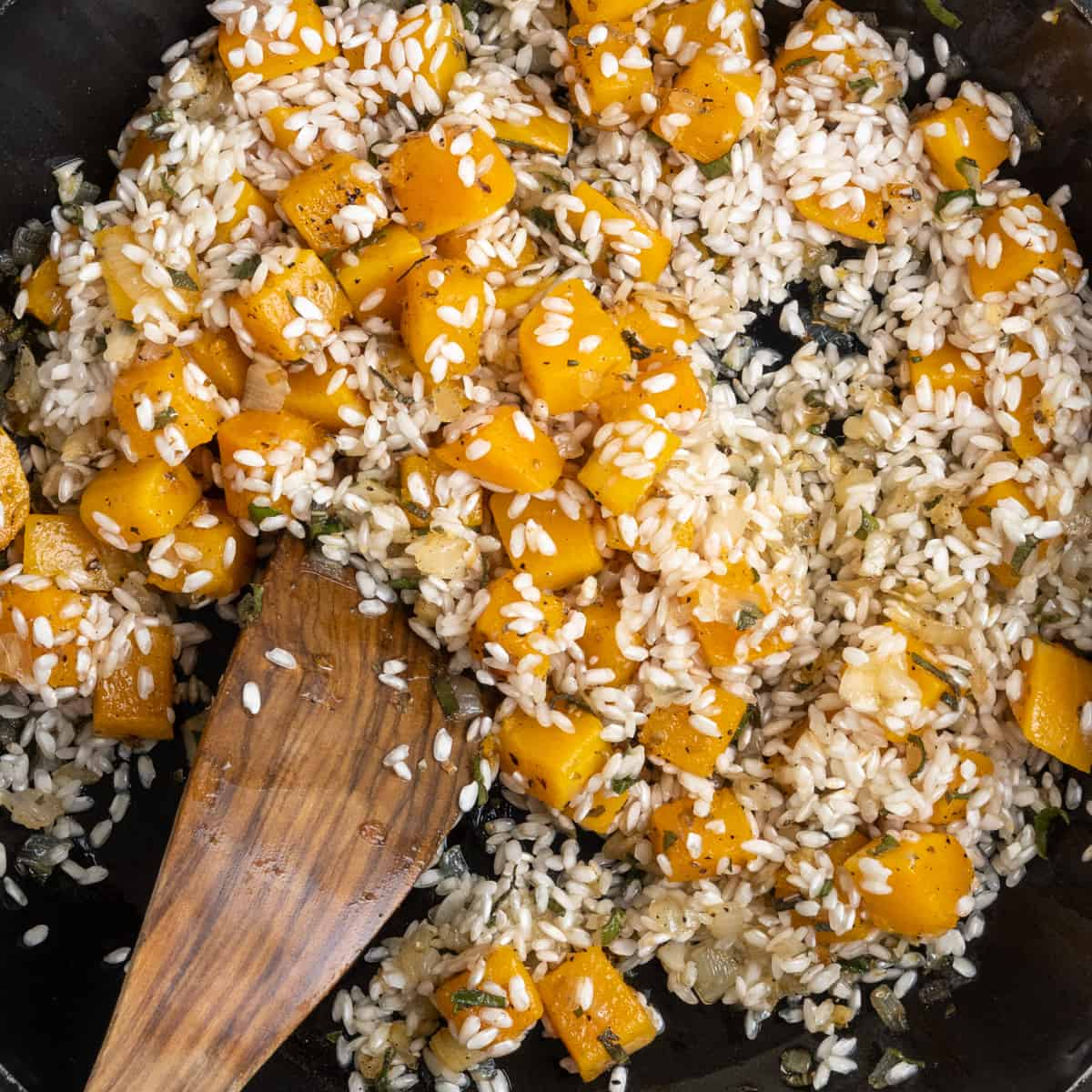 A spatula stirs the rice into the butternut squash and onion mixture.