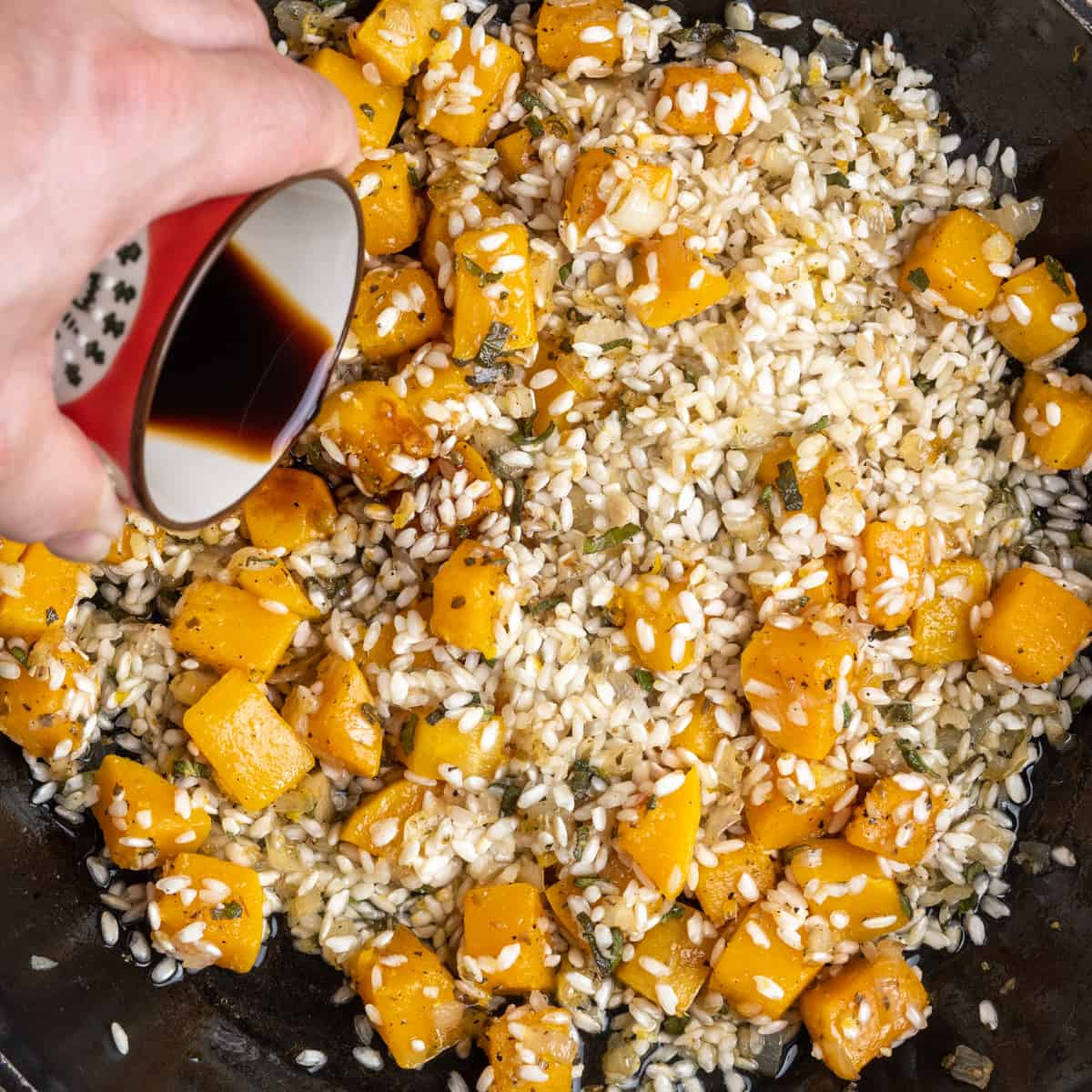 Pouring in soy sauce into the pan containing butternut and rice.