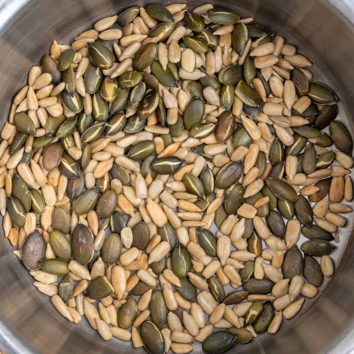 A pan with lightly golden toasted sunflower and pumpkin seeds.
