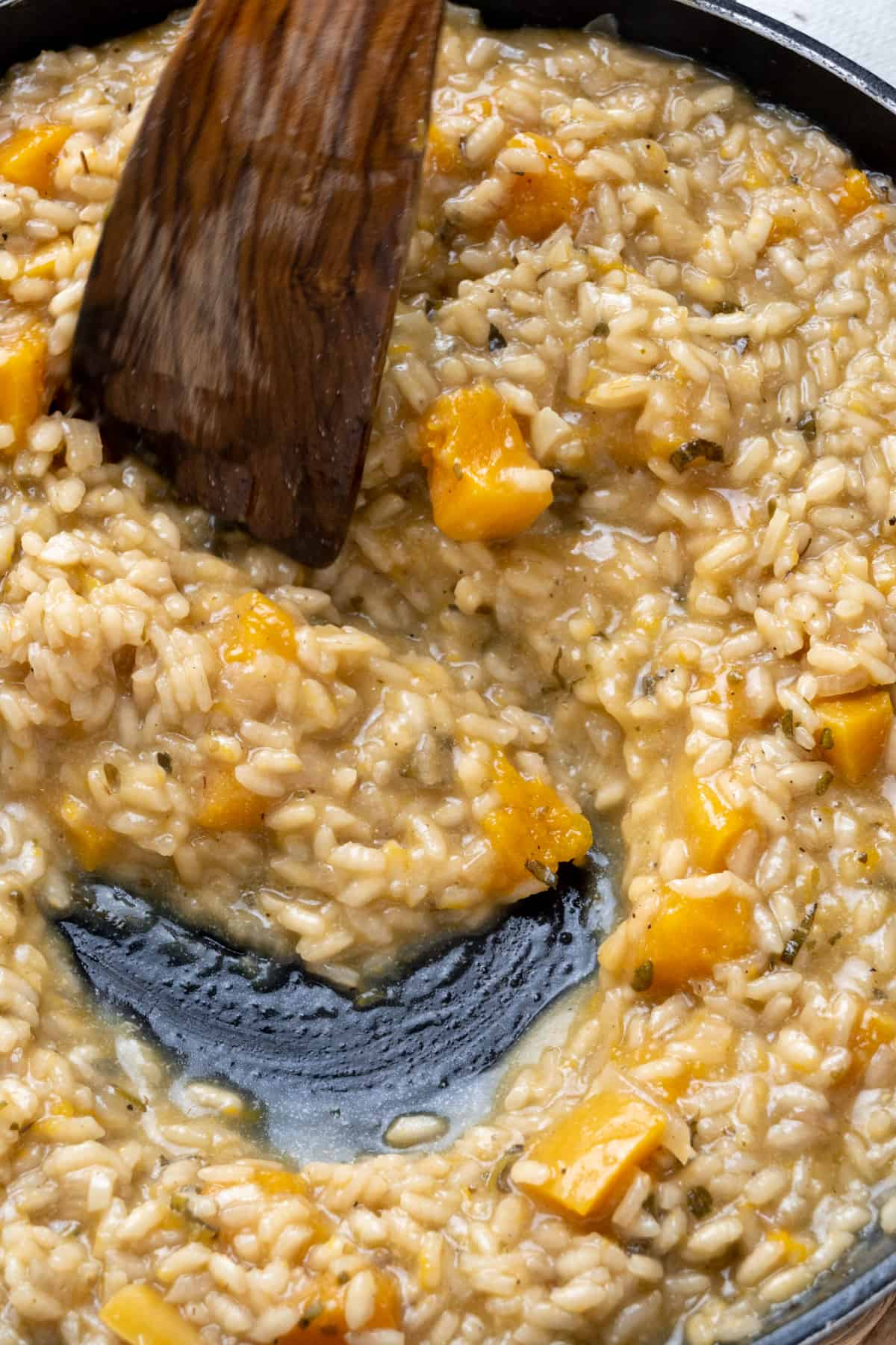 A spatula stirs the finished risotto, showing the creamy texture.