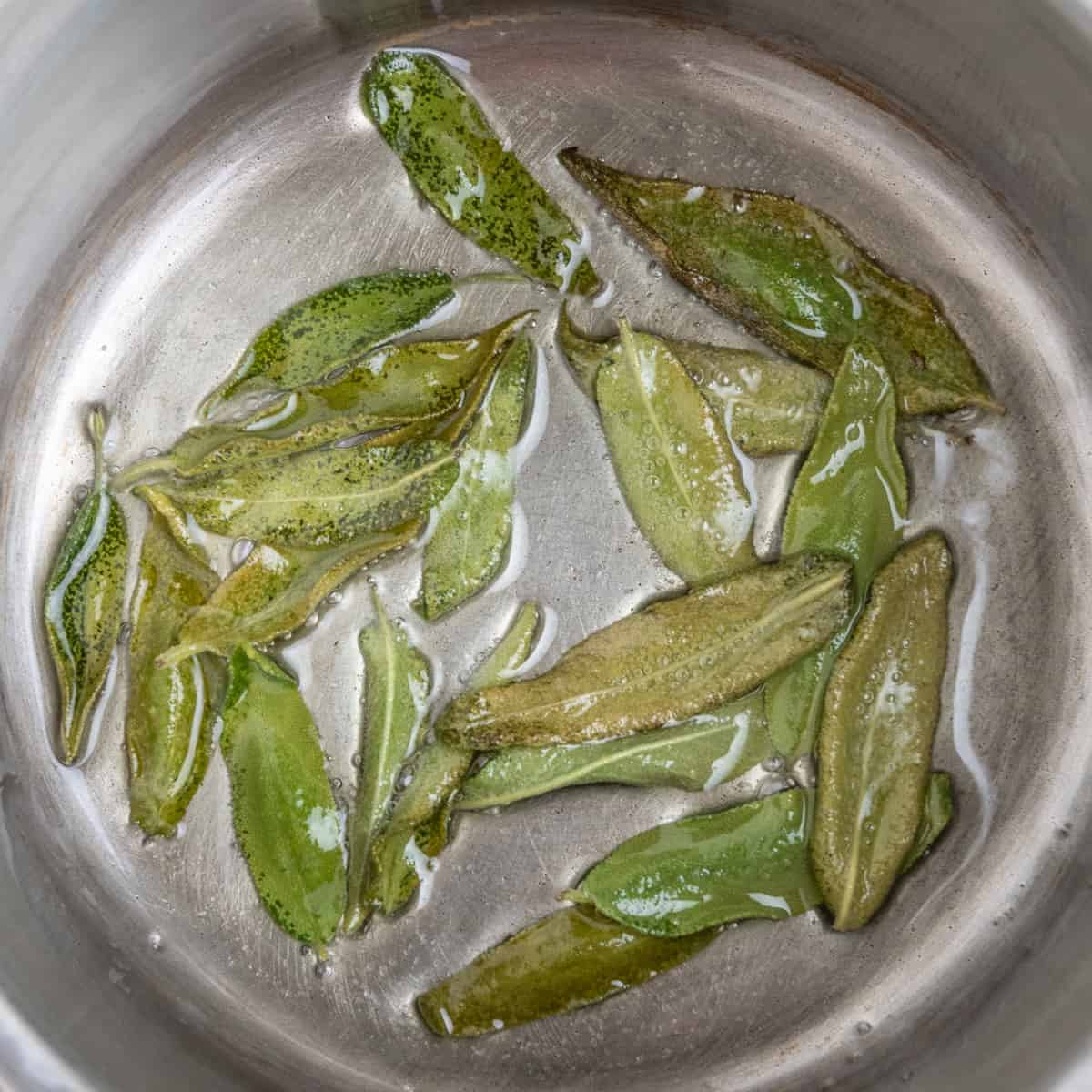 A steel pan continging sage leaves frying in oil.