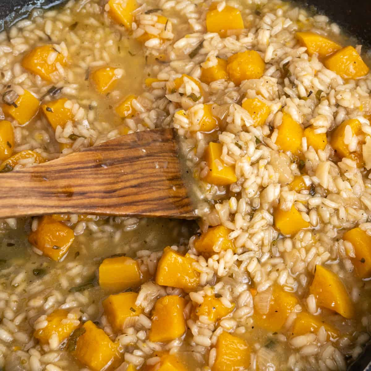 Rice grains and cubed squash cooking in a broth and stirred with a wooden spatula.