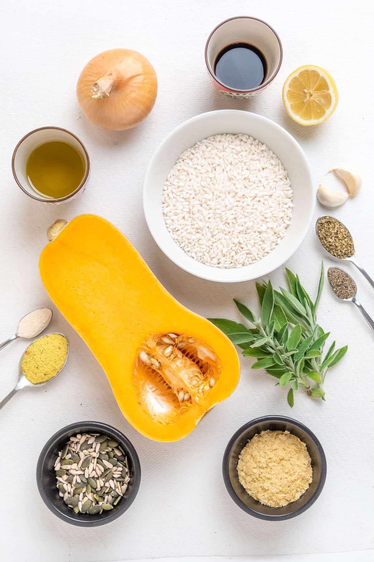 Ingredients for vegan butternut squash risotto on a white surface.