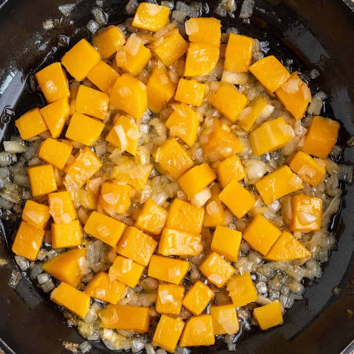 Sauteed butternut squash and onion in a pan.