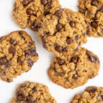 An overhead image of several oatmeal cookies with chocolate chips on a white surface.
