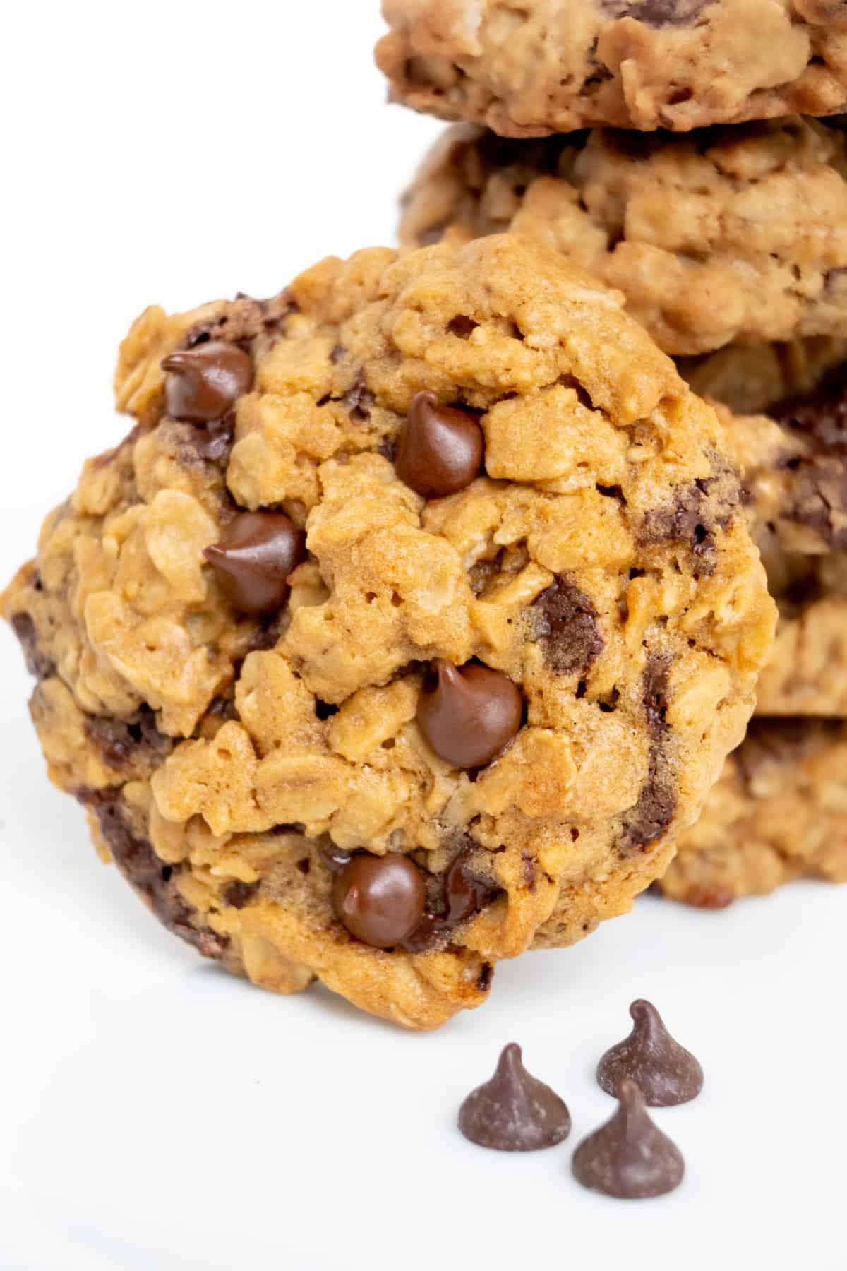 A crunchy and golden oatmeal cookie topped with chocolate chips leaning against a stack of more cookies.